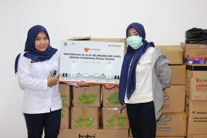 Tenaga medis Puskesmas Pulau Tidung berfoto bersama usai melakukan simbolis penyerahan bantuan CSR Bank DKI berupa 20 (dua puluh) Alat Pelindung Diri kepada Puskesmas Pulau Tidung dalam rangka penanganan pandemi virus Covid-19 di Jakarta, (1/4). Bank DKI juga akan memberikan APD kepada tenaga medis di RSUD-RSUD di DKI Jakarta. Selain memberikan APD, Bank DKI juga menyalurkan donasi kemanusiaan sebesar Rp190 juta yang diberikan kepada tenaga medis yang akan dikoordinasikan oleh Dinas Kesehatan.