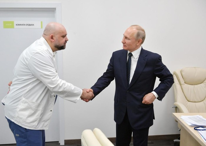 A picture taken on March 24, 2020 shows Russian President Vladimir Putin (R) shaking hands with the head of Moscows new hospital treating coronavirus (COVID-19) patients Denis Protsenko during his visit to Kommunarka hospital in Moscow. - The head of Moscows main coronavirus hospital who met with President Vladimir Putin a week ago has tested positive to the COVID-19, he said on March 31, as the Kremlin announced the Russian leaders health was fine. Denis Protsenko met with the Russian leader who inspected the Kommunarka hospital while wearing a bright yellow hazmat suit. But the 67-year-old Putin was also seen talking to Protsenko without any protective gear. (Photo by Alexey DRUZHININ / SPUTNIK / AFP)