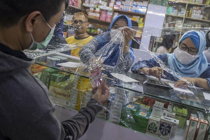 Seorang penjual melayani pembelinya di salah satu apotek di Jakarta, Kamis (2/4/2020).