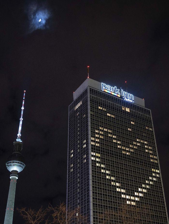 Park Inn Hotel di Berlin, Jerman, tidak lagi diizinkan menerima tamu seiring mewabahnya virus corona. Uniknya hotel ini memasang lampu berbentuk logo cinta di gedung mereka.