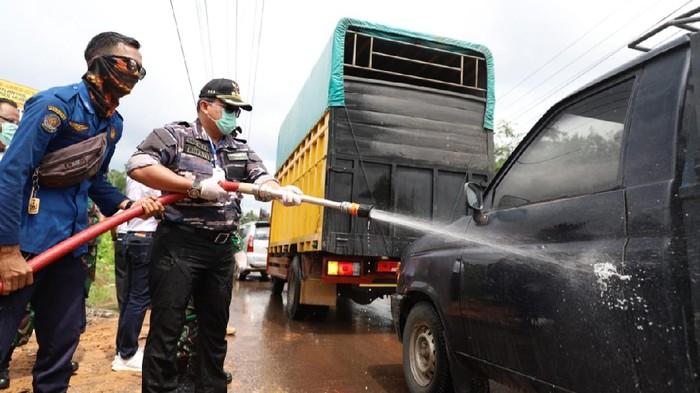 Bupati Musi Banyuasin Dodi Reza Alex saat menyemprot jalan dan kendaraan yang melintas.