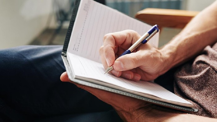 Close-up image of man enjoying moment for himself and filling diary after difficult day