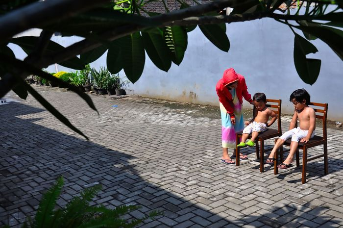 Seorang ibu menjemur kedua anaknya di bawah sinar matahari saat Self Isolation atau tinggal di rumah di Medan, Sumatera Utara, Minggu (22/3/2020). Berjemur diri di bawah matahari di antara pukul 08.00 WIB-11.00 WIB merupakan salah satu upaya yang paling sederhana untuk menjaga kesehatan selama wabah virus COVID-19. ANTARA FOTO/Septianda Perdana/foc.