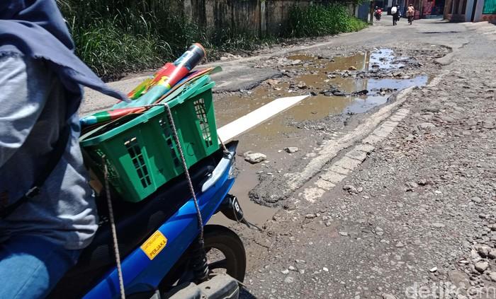 Jalan Raya Cibinong Tapos di perbatasan Cibinong-Depok tampak berlubang. Kendaraan pun terpaksa berjalan lambat saat melintasi jalan tersebut.