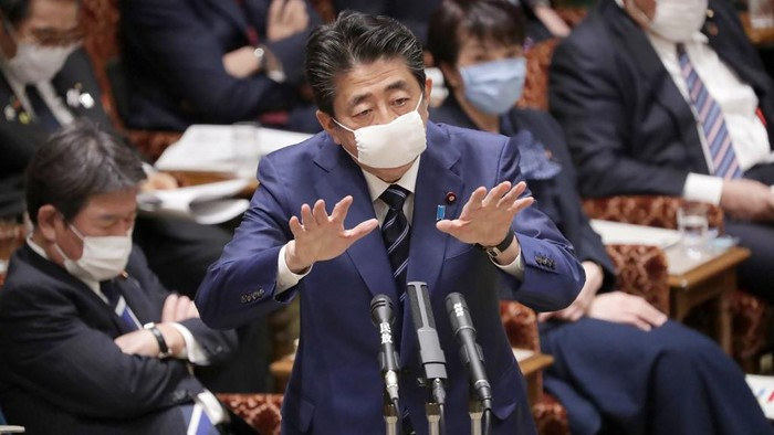 Japans Prime Minister Shinzo Abe, wearing a face mask amid concerns over the spread of COVID-19 coronavirus, attends an upper house committee meeting at the parliament in Tokyo on April 1, 2020. (Photo by STR / JIJI PRESS / AFP) / Japan OUT