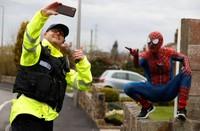 Baird juga mampir ke sekolah dasar dan menunjukan pose-pose ala Spider Man yang sering dilihat anak-anak di televisi. Dia juga berselfie dengan aparat kepolisisan yang berjaga. ( REUTERS/Phil Noble )