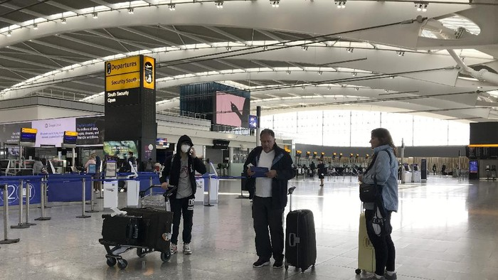 Passengers self distance as they wait at Heathrow Airport Terminal 5, in London, Tuesday, March 24, 2020. Britains Prime Minister Boris Johnson on Monday imposed its most draconian peacetime restrictions due to the spread of the coronavirus on businesses and social gatherings. For most people, the new coronavirus causes only mild or moderate symptoms. For some it can cause more severe illness.(AP Photo/Kirsty Wigglesworth)
