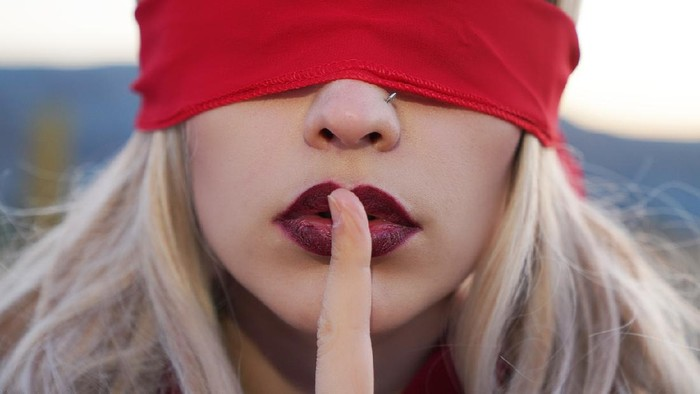 beautiful sensual woman with silence symbol. Woman blindfolded with red cloth silence symbol