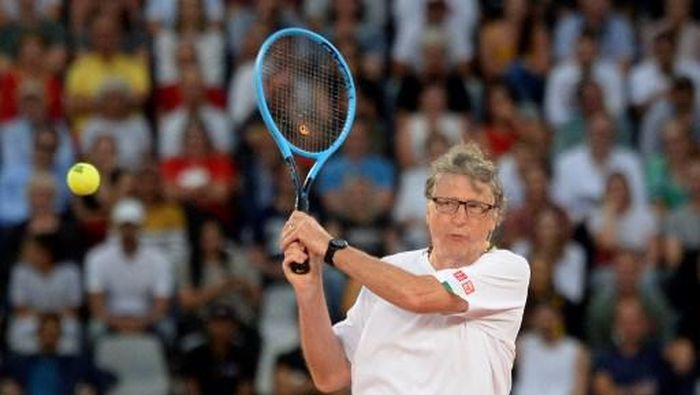 American philanthropist Bill Gates plays a return to Spains Rafael Nadal and South African Comedian Trevor Noah during their doubles tennis match at The Match in Africa at the Cape Town Stadium, in Cape Town on February 7, 2020. (Photo by RODGER BOSCH / AFP)