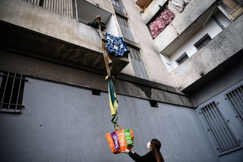 TOPSHOT - An inhabitant of the residence Maison Blanche (White House residence), composed of 226 mostly unsanitary dwellings, collects food offered by neighbours from his balcony, using a rope made with blankets, on March 31, 2020, in Marseille, southern France, on the fifteenth day of a lockdown aimed at curbing the spread of the COVID-19 (novel coronavirus). (Photo by Anne-Christine POUJOULAT / AFP) (Photo by ANNE-CHRISTINE POUJOULAT/AFP via Getty Images)