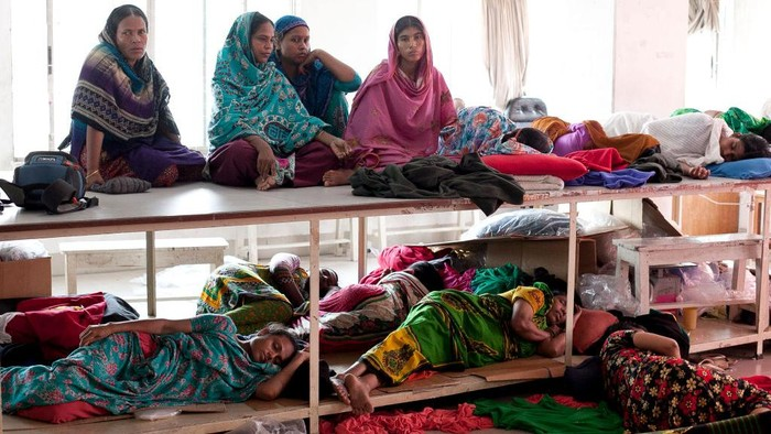 DHAKA, BANGLADESH - AUGUST 4: Women rest while participating in a hunger strike at a Tuba Group factory August 4, 2014 in Dhaka, Bangladesh. Garment workers have been on a hunger strike since July 28th, demanding three months of unpaid wages and Eid bonus from their employer, Tuba Group. (Photo by Allison Joyce/Getty Images)