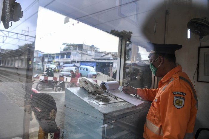 Petugas penjaga palang pintu kereta api Dedi (44) melakukan aktivitas kerja dari ruangannya di Jakarta, Sabtu (4/4/2020). Sejumlah warga masih melakukan aktivitas kerja di luar rumah seperti biasanya meski di saat pandemi COVID-19 agar tetap memberikan pelayanan kepada warga. ANTARA FOTO/Hafidz Mubarak A/hp.