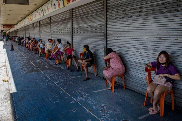 Para pembeli duduk di kursi yang sudah diberi jarak ketika mereka mengantri di luar sebuah swalayan toko pangan di Manila, Filipina, Jumat (3/4/2020).