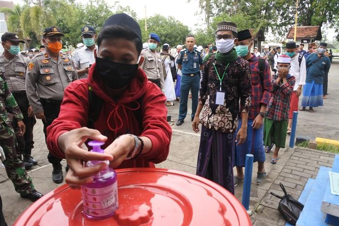 Sejumlah santri calon penumpang antre mencuci tangan sebelum memasuki KMP Dharma Bahari Sumekar III di area Pelabuhan Jangkar, Situbondo, Jawa Timur, Sabtu (4/4/2020). Kantor Kesyahbandaran dan Otoritas Pelabuhan (KSOP) Kelas IV Panarukan dan Pemkab Sumenep memfasilitasi pemulangan santri pondok pesantren sebanyak 566 orang asalPulau Kangean, sebagai upaya pencegahan penyebaran COVID-19. ANTARA FOTO/Seno/hp.
