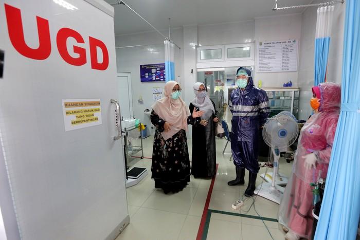 Ketua Komisi IV DPRK Banda Aceh Tati Meutia Asmara (kiri) berbincang dengan petugas medis Puskesmas Meuraxa yang memakai jas hujan plastik sebagai Alat Pelindung Diri (APD) untuk melayani pasien di Banda Aceh, Aceh, Senin (6/4/2020). Petugas medis di tingkat puskesmas terpaksa menggunakan jas hujan karena keterbatasan APD yang sesuai standar guna mencegah penularan virus Corona (COVID-19). ANTARA FOTO/Irwansyah Putra/wsj.