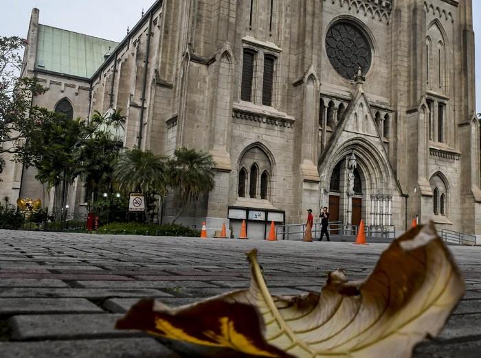 Petugas kebersihan melintas di depan pintu Gereja Katedral, Jakarta, Minggu (5/4/2020). Pasca Kemenkes resmi merilis Peraturan Menteri Kesehatan No.9 Tahun 2020 tentang Pembatasan Sosial Berskala besar (PSBB) dalam Rangka Percepatan Penanganan COVID-19, bentuk ibadah misa gereja dilakukan secara live streaming melalui media sosial, termasuk rangkaian ibadah paskah yang akan jatuh mulai Kamis (16/4/2020) hingga Minggu (19/4/2020). ANTARA FOTO/Muhammad Adimaja/foc.
