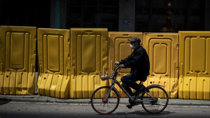 A face mask-clad cyclist rides alongside a barricade separating a residential compound in Wuhan, Chinas central Hubei province on April 6, 2020, after some restrictions amid the COVID-19 coronavirus pandemic were eased in the city. (Photo by NOEL CELIS / AFP)