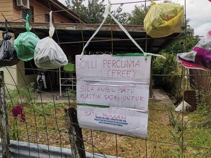 Warga melintas di depan pintu masuk Kampung Pucang Sewu yang melakukan karantina wilayah, Surabaya, Jawa Timur, Minggu (5/4/2020). Karantina wilayah tersebut dilakukan oleh warga di kampung itu guna mencegah penyebaran Virus Corona (COVID-19). ANTARA FOTO/Zabur Karuru/foc.