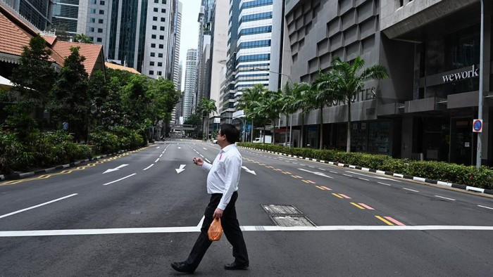 A man crosses an empty street in the central business district of Singapore on April 7, 2020, as the country ordered the closure of all businesses deemed non-essential as well as schools to combat the spread of the COVID-19 novel coronavirus. - Singapores usually bustling business district was almost deserted on April 7 as most workplaces in the city-state closed to stem the spread of the coronavirus after a surge in cases. (Photo by Roslan RAHMAN / AFP)