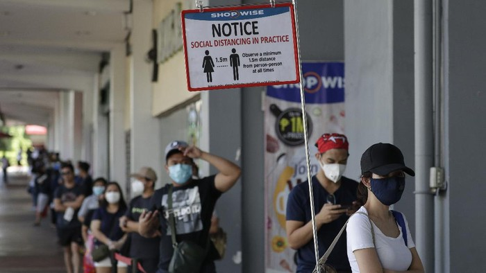 A reminder stands beside a long line of people wearing protective masks outside a supermarket during a community quarantine to help curb the spread of the new coronavirus in Manila, Philippines on Wednesday, April 1, 2020. The new coronavirus causes mild or moderate symptoms for most people, but for some, especially older adults and people with existing health problems, it can cause more severe illness or death. (AP Photo/Aaron Favila)