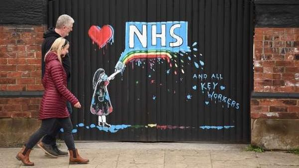Graffiti yang menggambarkan logo Layanan Kesehatan Nasional Inggris (NHS) dan pelangi, sebagai tanda cinta dan terima kasih kepada staf NHS dan semua pihak yang terlibat dalam merawat pasien Covid-19, digambarkan di gerbang ke sebuah pub tertutup di Pontefract, Inggris (Oli Scarff/AFP)