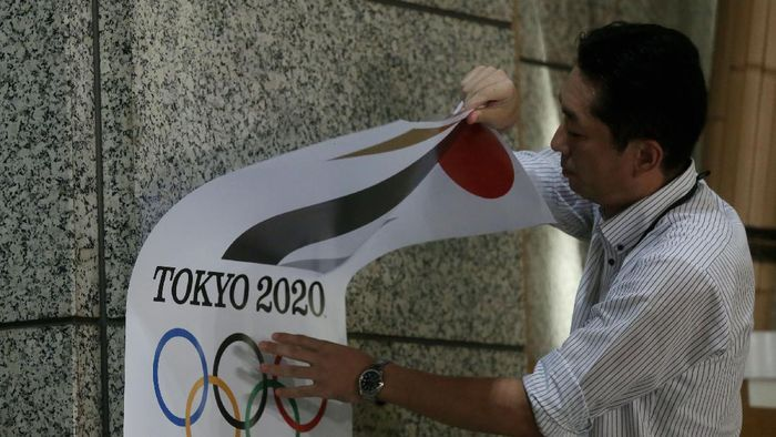 TOKYO, JAPAN - SEPTEMBER 01:  An employee removes a Tokyo 2020 Olympic poster showing the copied logo design hung at the entrance of the Tokyo Metropolitan Government Office building during an event staged for the media on September 1, 2015 in Tokyo, Japan. The 2020 Tokyo Olympics organizing committee announced after an emergency meeting that it will cease using the logo after it was found to have been plagiarized by designer Kenjiro Sano.  (Photo by Chris McGrath/Getty Images)