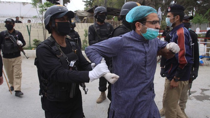 Police arrest doctors demanding facilities and prevention kits to attend coronavirus patients in Quetta, Pakistan, Monday, April 6, 2020. The government imposed a nationwide lockdown to try to contain the outbreak of the virus. (AP Photo/Arshad Butt)