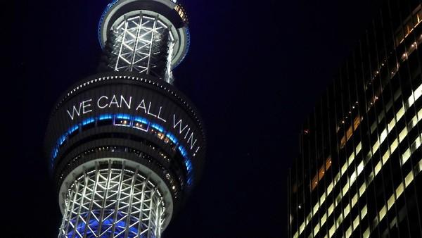 Di tengah pandemi corona, Tokyo Skytree di Jepang menuliskan pesan berupa bersama kita semua bisa menang melawan virus corona. Bentuk dukungan ini muncul setelah PM Jepang Shinzo Abe menyatakan perlawanan pada corona (Issei Kato/Reuters)