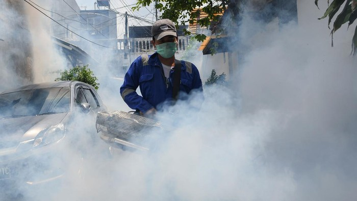 Warga menutup wajahnya dengan kaos saat berlangsungnya pengasapan (fogging) di kawasan Pasar baru, Jakarta, Selasa (7/4/2020). Kegiatan tersebut guna memberantas nyamuk Aedes aegypti sekaligus mencegah wabah demam berdarah dengue (DBD). ANTARA FOTO/M Risyal Hidayat/foc.
