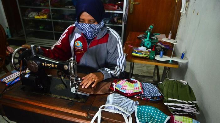 Relawan menunjukkan masker hasil produksinya di Gondangmanis, Kudus, Jawa Tengah, Senin (6/4/2020). Masker yang diproduksi dari bahan kain perca tersebut akan didistribusikan secara gratis kepada masyarakat yang membutuhkan guna mencegah penyebaran COVID-19. ANTARA FOTO/Yusuf Nugroho/wsj.