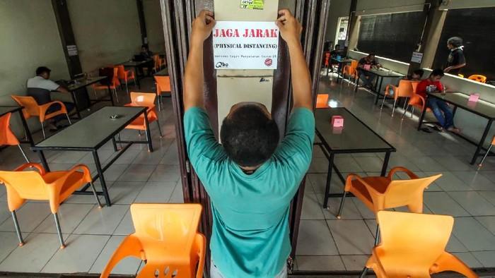 Pelanggan duduk berjarak saat menunggu makanan pesanannya di sebuah restoran cepat saji di Surabaya, Jawa Timur, Senin (6/4/3/2020). Sejumlah restoran di Surabaya memilih tetap buka namun hanya melayani pesanan untuk dibawa pulang guna mencegah penyebaran Virus Corona (COVID-19). ANTARA FOTO/Zabur Karuru/wsj.