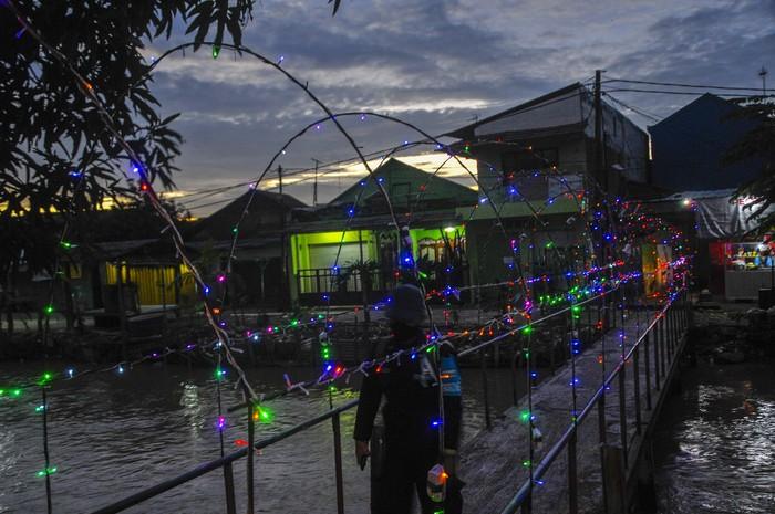 Warga melintasi jembatan di kampung pintu air, Bekasi, Jawa Barat,  Selasa (7/4/2020). Pemerintah kota Bekasi memperketat kebijakan pembatasan sosial dengan menghalau warga yang masih berkumpul diatas pukul 21.00 WIB untuk mencegah penyebaran COVID-19. ANTARA FOTO/ Fakhri Hermansyah/hp.