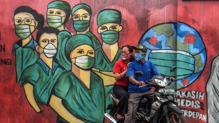 Pengendara motor melintas di depan mural tentang pandemi virus corona atau COVID-19 di Jalan Raya Jakarta-Bogor, Depok, Jawa Barat, Jumar (3/4/2020). Mural tersebut ditujukan sebagai bentuk dukungan kepada tenaga medis yang menjadi garda terdepan dalam menghadapi COVID-19 di Indonesia. ANTARA FOTO/Yulius Satria Wijaya/pras.