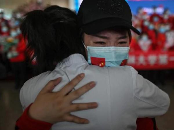 Anggota staf medis Provinsi Jilin menangis saat memeluk perawat dari Wuhan setelah lockdown berakhir. (AFP)