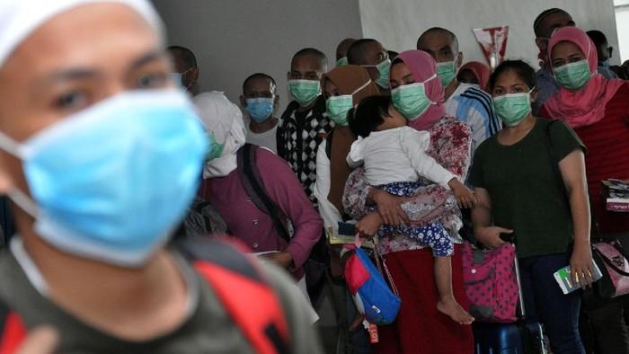 Petugas Karantina Kemenkes memeriksa surat kesehatan kewaspadaan para Tenaga Kerja Indonesia (TKI) dari Malaysia  saat tiba di Bandara Internasional Kualanamu Kabupaten Deliserdang, Sumatera Utara, Kamis (9/4/2020). Sebanyak 134 orang TKI yang terdampak lockdown atau karantina wilayah COVID-19 di Malaysia tersebut selanjutnya akan mengikuti proses karantina di bawah pengawasan Gugus Tugas Percepatan Penanganan COVID-19 Sumut sebelum dipulangkan ke daerah asal mereka masing-masing. ANTARA FOTO/Septianda Perdana/nz