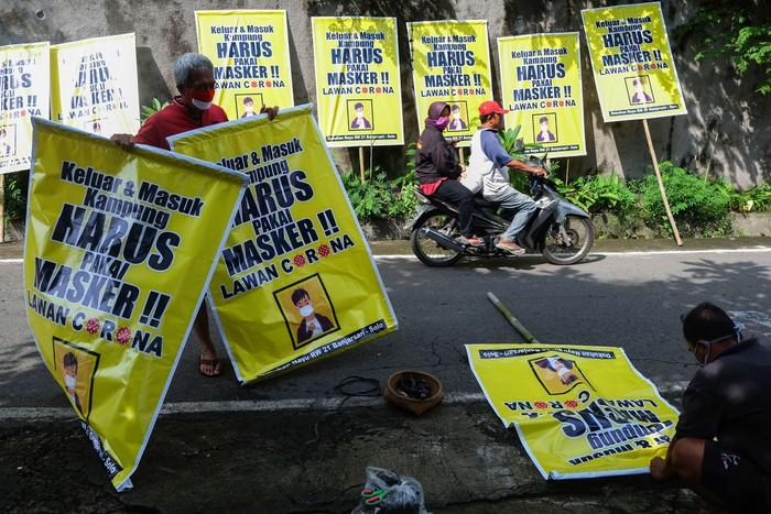 Warga bergotong royong memasang poster imbauan untuk memakai masker saat beraktivitas di Kampung Nayu, Banjarsari, Solo, Jawa Tengah, Rabu (8/4/2020). Pemasangan poster tersebut sebagai usaha warga setempat mencegah penyebaran virus COVID-19. ANTARA FOTO/Maulana Surya/aww.