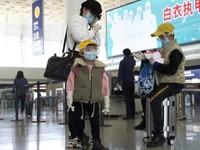 Seorang ibu dan dua orang anak memakai kaca mata dan masker menunggu penerbangan di Bandara Internasional wuhan Tianhe. (AP)