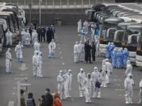 Para pelancong dari Wuhan berkumpul untuk naik bis saat mereka tiba di Beijing untuk melakukan karantina selama 14 hari. (AFP)