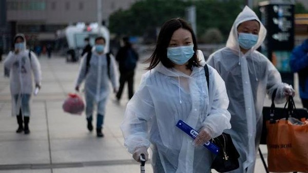 Para penumpang tiba di Stasiun Kereta Api Hankou, Wuhan. Menggunakan masker dan jas hujan, mereka ingin mengambil salah satu kereta pertama yang meninggalkan kota di provinsi Hubei. (AFP)