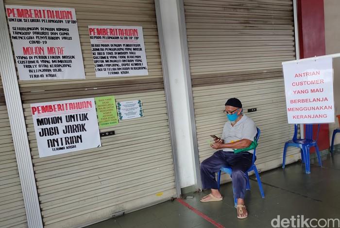 Warga mengantre memasuki pusat perbelanjaan di kawaasan Pondok Gede, Bekasi,  Jawa Barat, Kamis (9/4/2020).