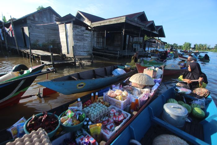 Pedagang bertransaksi dengan warga di pasar terapung Lok Baintan, Desa Lok Baintan, Kabupaten Banjar, Kalimantan Selatan, Jumat (10/4/2020).