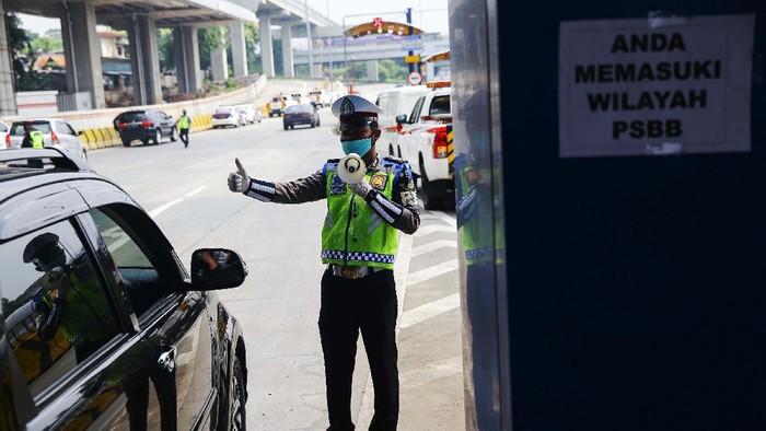 Petugas kepolisian melakukan pengecekan kepada kendaraan yang melintasi gerbang tol Pasar Rebo Utama. Ini bagian dari penerapan PSBB di Jakarta.