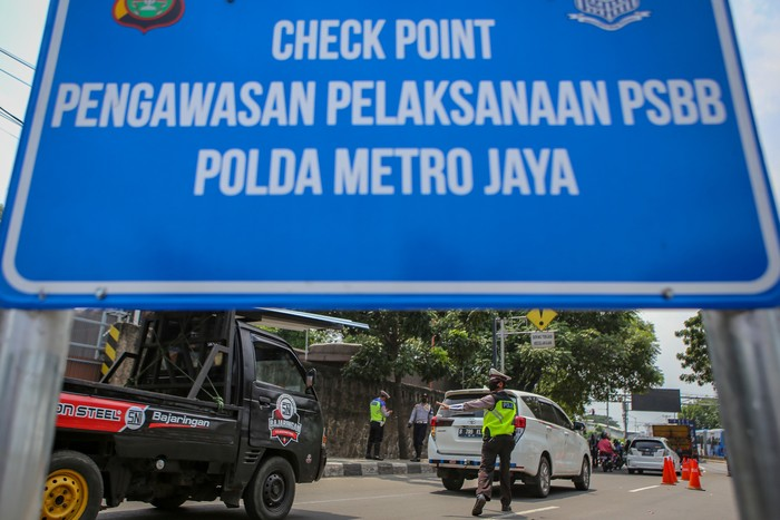 Polisi berjaga di sejumlah perbatasan di DKI Jakarta di hari pertama penerapan Pembatasan Sosial Berskala Besar (PSBB). Polisi mengingatkan warga untuk memakai masker.