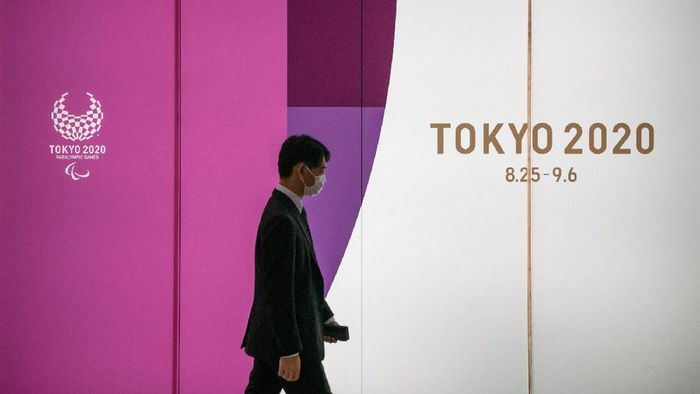 Japanese Government And IOC Agree To Postpone Olympic Games TOKYO, JAPAN - MARCH 25: A man passes an advert for the Tokyo 2020 Olympics on March 25, 2020 in Tokyo, Japan. Following yesterdays announcement that the Tokyo 2020 Olympics will be postponed to 2021 because of the ongoing Covid-19 coronavirus pandemic, IOC officials have said they hope to confirm a new Olympics date as soon as possible. (Photo by Carl Court/Getty Images)