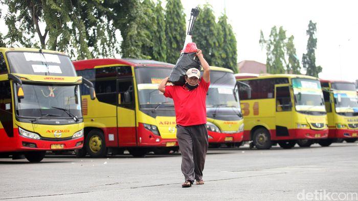 Warga memanggul barang-barangnya di Terminal Kalideres, Jakarta Barat, Jumat (10/4/2020).