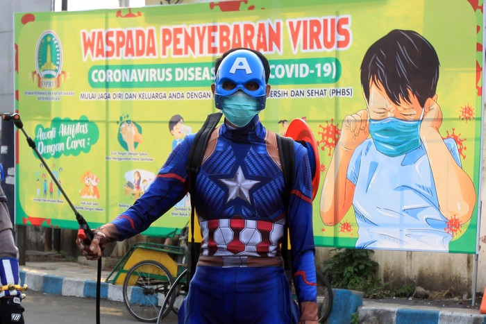 Sejumlah petugas kepolisian yng berpakaian superhero menyemprotkan cairan disinfektan di jalan Panglima Sudirman kawasan Kebonagung, Pasuruan, Jawa Timur, Kamis (9/4/2020). Penyemprotan cairan disinfektan tersebut bertujuan untuk mengantisipasi penyebaran Virus Corona (COVID-19). ANTARA FOTO/Umarul Faruq/aww.