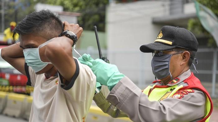 Polisi melakukan imbauan kepada pengendara mobil untuk dapat mematuhi penerapan Pembatasan Sosial Berskala Besar (PSBB) di kawasan Menteng, Jakarta (11/4/2020). Iimbauan ini dilakukan agar masyarakat menerapkan pembatasan sosial berskala besar (PSBB) selama 14 hari, yang salah satu aturannya adalah pembatasan penumpang kendaraan serta anjuran untuk menggunakan masker jika berkendara. ANTARA FOTO/Nova Wahyudi/hp.
