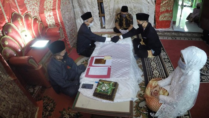 Penghulu memberikan buku nikah kepada pasangan  pengantin, saat prosesi pernikahan, di Balai Nikah Kantor Urusan Agama (KUA) Padang Barat, Kota Padang, Sumatera Barat, Sabtu (11/4/2020). Penyelenggaraan pernikahan tetap dilaksanakan di kantor KUA setempat dengan mematuhi protokol pencegahan COVID-19 sesuai panduan dari Kementerian Agama, di antaranya tidak boleh lebih dari 10 orang dan harus menggunakan masker serta sarung tangan. ANTARA FOTO/Iggoy el Fitra/hp.