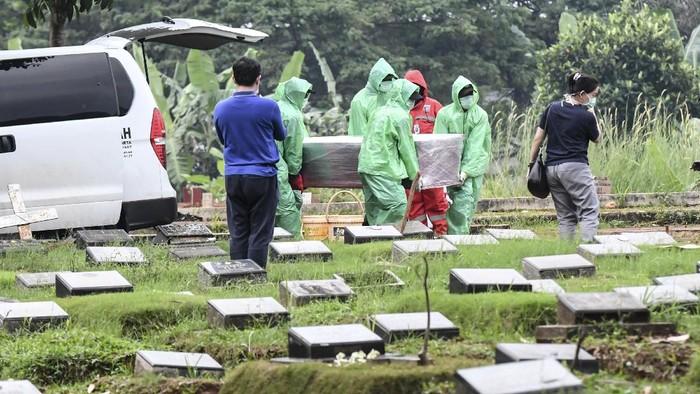 Petugas pemakaman membawa peti jenazah pasien COVID-19 di TPU Pondok Ranggon, Jakarta, Senin (30/3/2020). Juru bicara pemerintah untuk penanganan COVID-19 Achmad Yurianto per Senin (30/3/2020) pukul 12.00 WIB menyatakan jumlah pasien positif COVID-19 di Indonesia telah mencapai 1.414  kasus, pasien yang telah dinyatakan sembuh sebanyak 75 orang, sementara kasus kematian bertambah delapan orang dari sebelumnya 114 orang menjadi 122 orang.