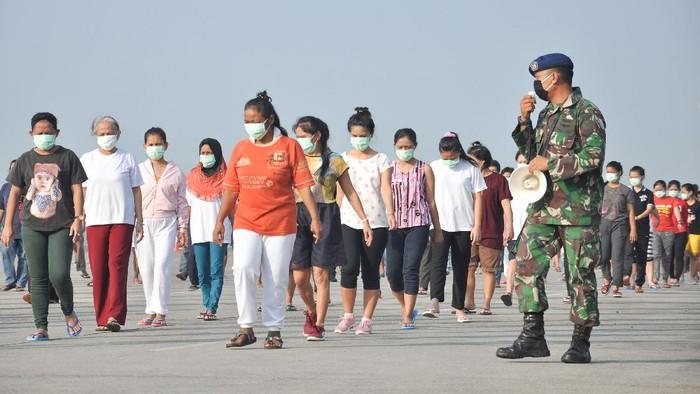 Sejumlah Tenaga Kerja Indonesia (TKI) asal Malaysia mengikuti senam dan berjemur di bawah sinar matahari saat menjalani karantina di Pangkalan Udara Militer (Lanud) Soewondo Medan, Sumatera Utara, Sabtu (11/4/2020). Sebanyak 513 TKI yang berasal dari berbagai daerah di Sumut dan sekitarnya yang menjalani proses karantina COVID-19 sementara tersebut saat ini kondisi kesehatannya baik dan tidak ada menunjukan gejala infeksi seperti demam, batuk dan sesak nafas. ANTARA FOTO/Septianda Perdana/hp.